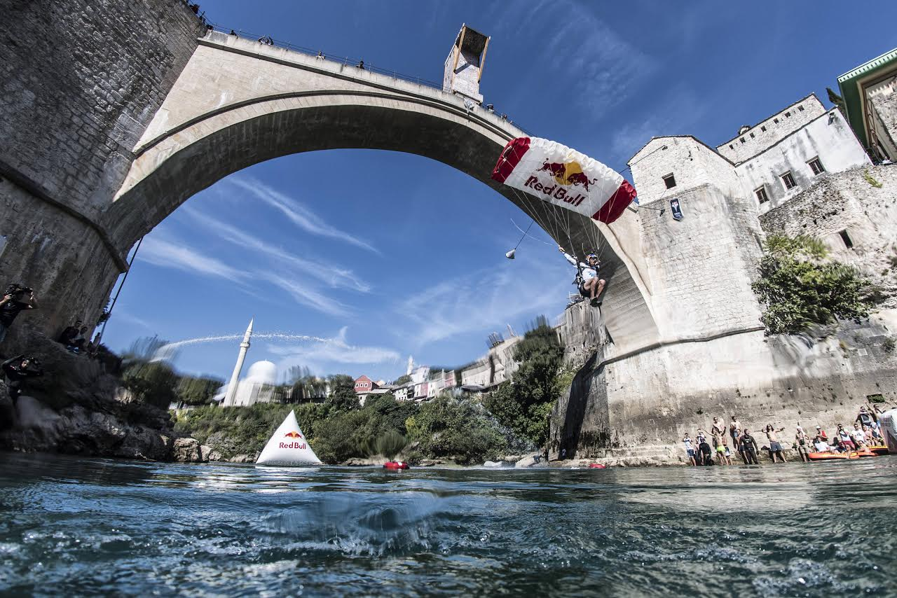 Skydive team member Marco Waltenspiel of Austria flies under the Stari Most during the seventh stop of the Red Bull Cliff Diving World Series in Mostar, Bosnia & Herzegovina on September 24, 2016. // Predrag Vuckovic/Red Bull Content Pool // P-20160924-00379 // Usage for editorial use only // Please go to www.redbullcontentpool.com for further information. //
